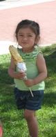 girl eating corn on stick