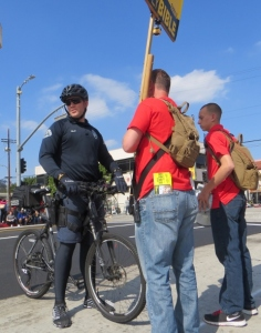Policeman telling two roving prechers that they have to walk on the sidewalk, not on the parade route.