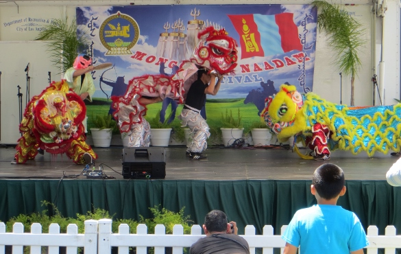 Lion dancers on stage at the Lotus Festival. A drum, cymbals made for lots of noise.