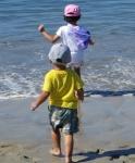 children dashing into ocean