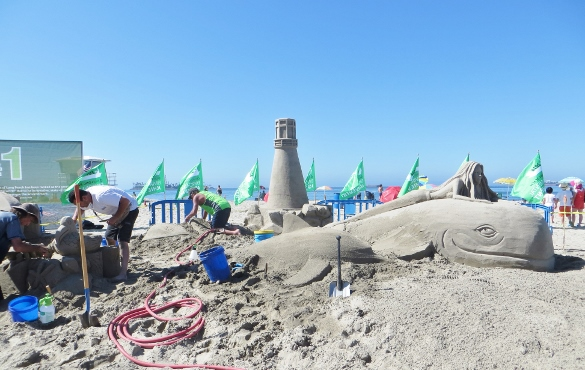 The Port of Long Beach hired a group of professional sand sculptors to create the Pt. Fermin lighthouse, a mermaid riding a whale, and other sea creatures. It had taken them 2 days to get this far and they weren't done yet.